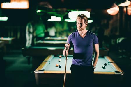 cue sticks: Young man playing pool