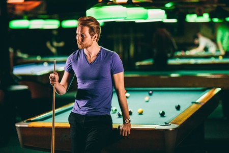 snooker room: Young man playing pool