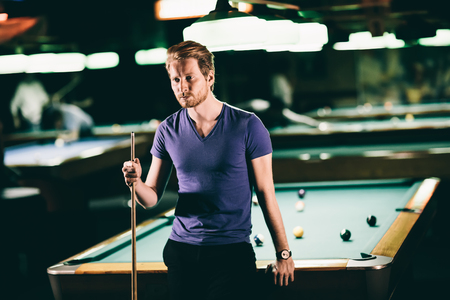 billiards room: Young man playing pool