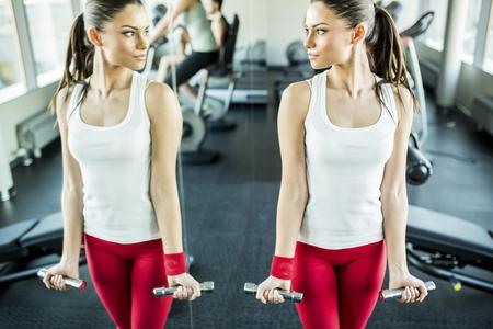 levantar pesas: Entrenamiento de la mujer joven en el gimnasio por el espejo