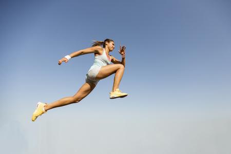 salto de longitud: Mujer joven que toma el salto de longitud