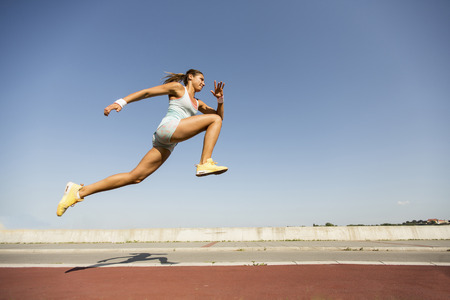 is long: Young woman taking long jump Stock Photo