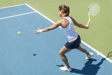 jugando: Mujer joven que juega al tenis