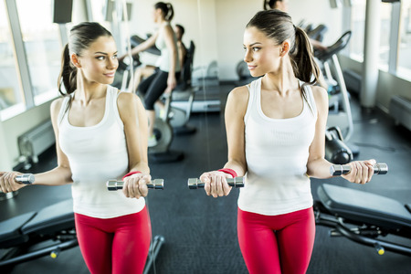 Young woman training in the gym by the mirror Stock Photo