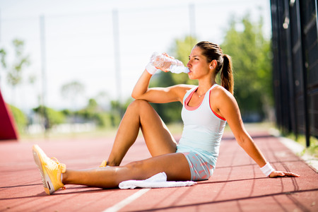 drink: Sporty young woman drinking water