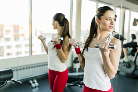 sport fitness: Young woman training in the gym by the mirror Stock Photo
