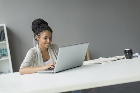 Jonge vrouw in het kantoor Stockfoto