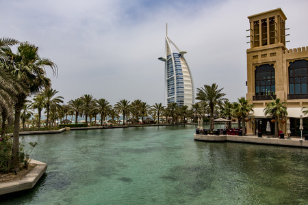 encompasses: DUBAI, UAE - MAY 8, 2015: Unidentified people at Madinat Jumeirah in Dubai. Madinat Jumeirah encompasses two hotels and clusters of 29 traditional Arabic houses.