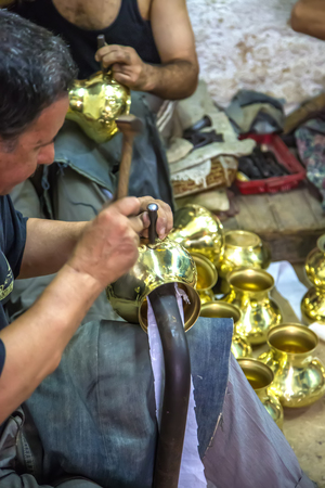 he is a traditional: FES, MOROCCO - September 15, 2014 : Unknown man working as handcraftsman at workshop in Fes, Morocco. He makes their traditional souvenirs.