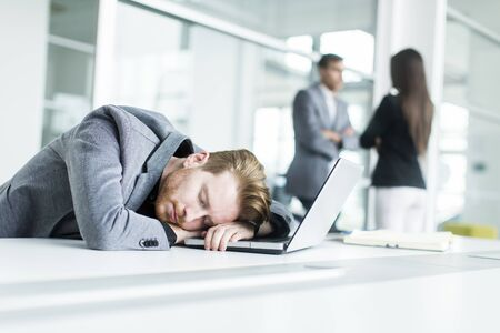 tired businessman: Tired young man sleeping in the office Stock Photo