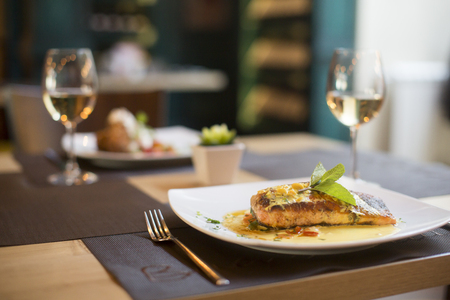 Grilled salmon with sauce and herbs served at restaurant Stock Photo