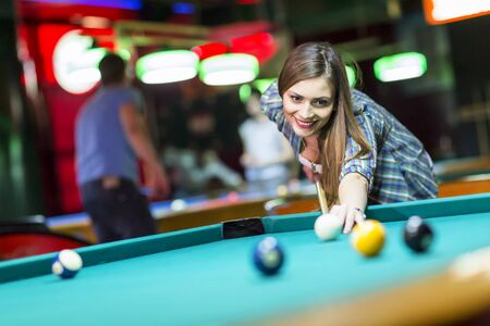 cue sticks: Young woman playing pool Stock Photo