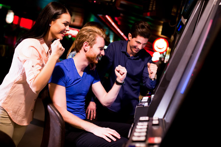 slot machine: Young people at slot machine in the casino