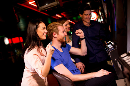 Los jóvenes en la máquina tragaperras en el casino