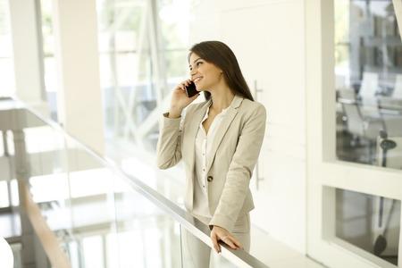 オフィスで携帯電話を持つ若い女性