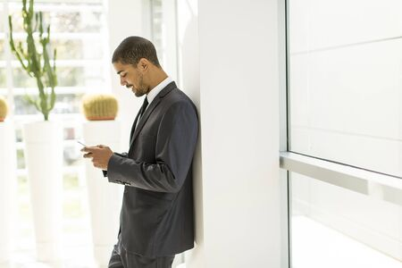 african business: Handsome young black man with mobile phone in the office