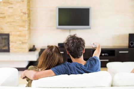 mujer viendo tv: Pareja joven viendo la televisión Foto de archivo