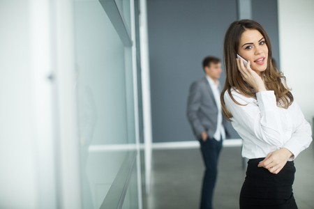 woman at the phone: Young woman in office with mobile phone Stock Photo