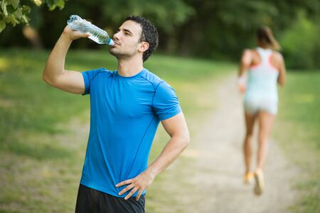 man drinking water: Young man drinking water outdoors Stock Photo