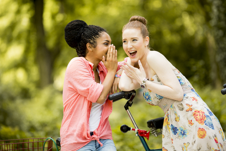 affectionate actions: Young women posing by the bicycle