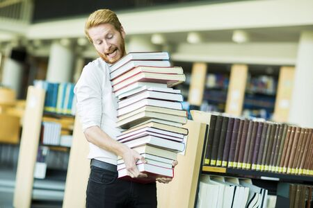 choose university: Young man in the library Stock Photo