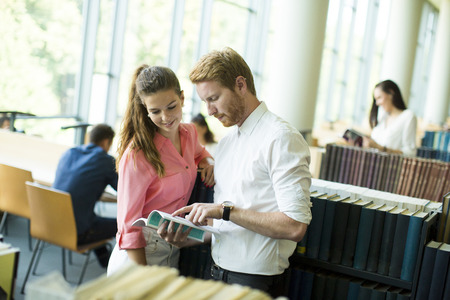 student studying: Young couple in the library