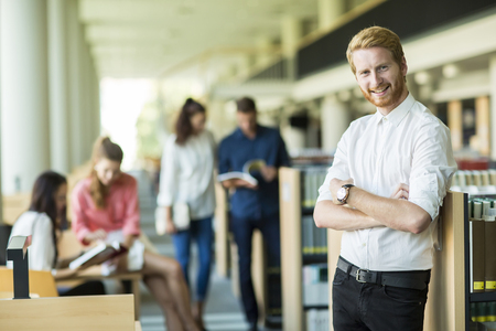 university choice: Young man in the library Stock Photo