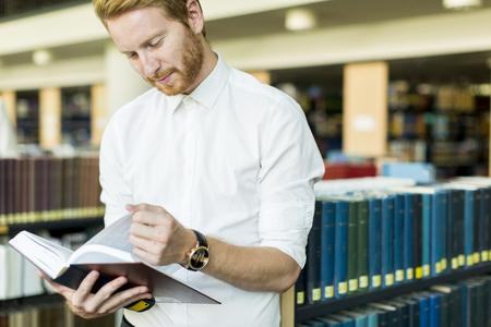 biblioteca: Hombre joven en la biblioteca Foto de archivo