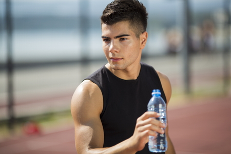 man drinking water: Young man drinking water at summer