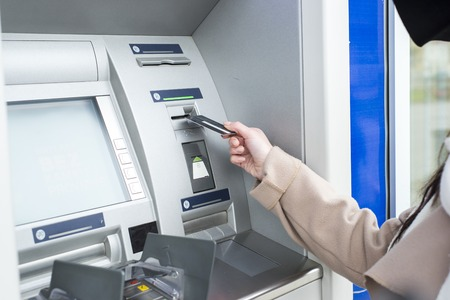 automatic transaction machine: Young woman using the ATM