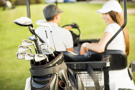 Young couple at golf cart 스톡 콘텐츠
