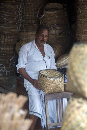 18 20: VARKALA, INDIA - OCTOBER 18, 2015: Unidentified bamboo basket maker in Varkala, India. Bamboo- based  industries in India provide employment to about 20 million people.
