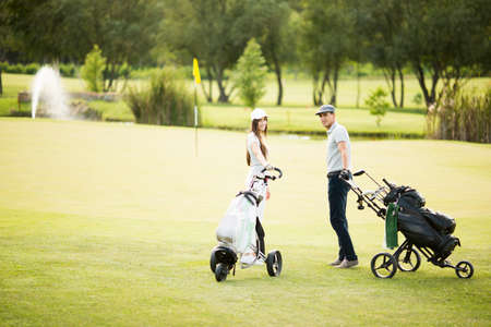 golf bag: Young couple at golf cart Stock Photo