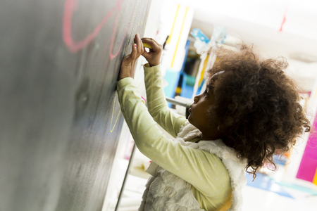 playroom: Little african girl drawing on the board