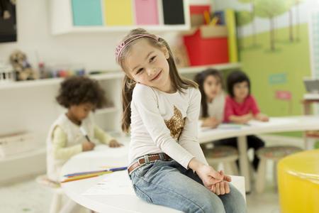 Enfants multiraciaux dessinant dans la salle de jeux Banque d'images - 52571605