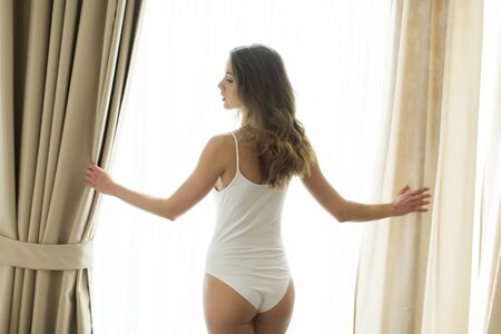 adult young: Girl posing in underwear by the window