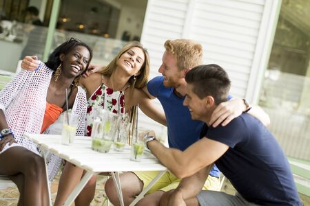 multiracial: Young multiracial friends at cafe Stock Photo