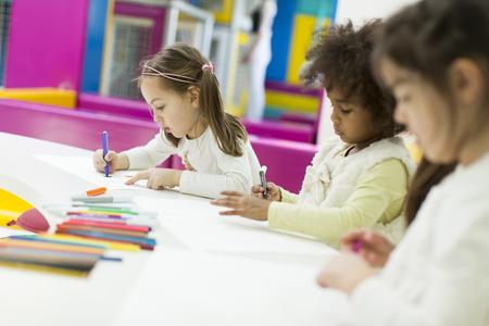 Enfants Multiracial dessin dans la salle de jeux Banque d'images - 52575946