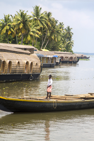 backwaters: KERALA, INDIA - OCTOBER 16, 2015: Unindetified man at backwaters in Kerala, India. The backwaters are an extensive network of 41 west flowing interlocking rivers, lakes and canals that center around Alleppey, Kumarakom and Punnamada.
