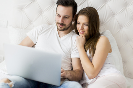 in: Young couple with laptop in the bed