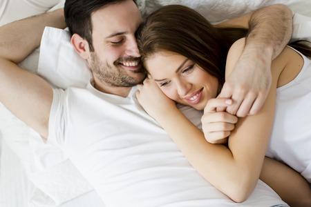 pareja en la cama: Pareja joven amante en la cama