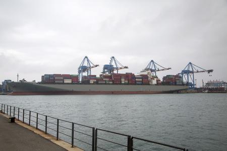 sea seaport: GENOA, ITALY - MAY 2, 2015: Cargo ship at Genoa port in Italy. The Port of Genoa is a major Italian seaport on the Mediterranean Sea.