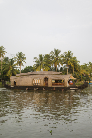 alleppey: KERALA, INDIA - OCTOBER 16, 2015: Unindetified people at backwaters in Kerala, India. The backwaters are an extensive network of 41 west flowing interlocking rivers, lakes and canals that center around Alleppey, Kumarakom and Punnamada. Editorial