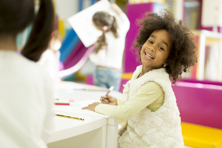 girl drawing: Multiracial children drawing in the playroom Stock Photo