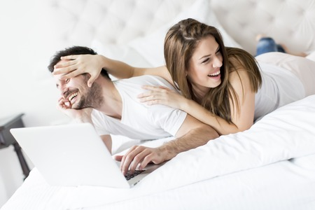 couples in love: Young couple with laptop in the bed