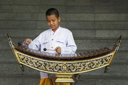 バンコク, タイ王国 - 2016 年 2 月 14 日: 正体不明の少年、バンコクの路上で木琴を演奏します。Ranat と呼ばれる木製の木琴は、古典音楽の最も重要な