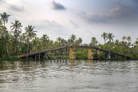 allepey: KERALA, INDIA - OCTOBER 16, 2015: Unindetified man at backwaters in Kerala, India. The backwaters are an extensive network of 41 west flowing interlocking rivers, lakes and canals that center around Alleppey, Kumarakom and Punnamada.