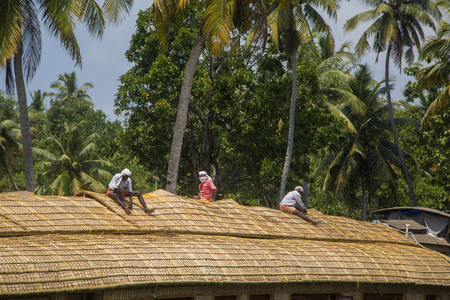 alleppey: KERALA, INDIA - OCTOBER 16, 2015: Unindetified men at backwaters in Kerala, India. The backwaters are an extensive network of 41 west flowing interlocking rivers, lakes and canals that center around Alleppey, Kumarakom and Punnamada. Editorial