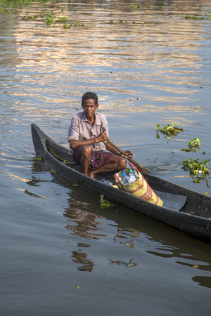 backwaters: KERALA, INDIA - OCTOBER 17, 2015: Unindetified man at backwaters in Kerala, India. The backwaters are an extensive network of 41 west flowing interlocking rivers, lakes and canals that center around Alleppey, Kumarakom and Punnamada.