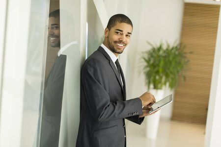 black professional: Young black man with tablet in the office Stock Photo